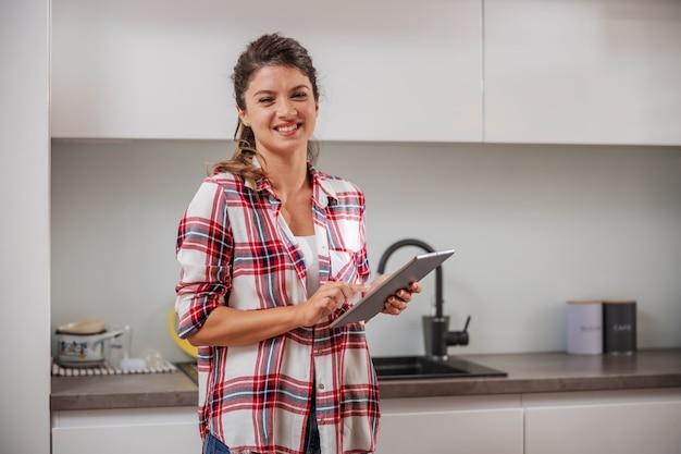 Lächelnde junge frau, die in der küche steht und tablette verwendet.