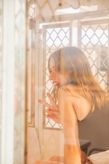 Lächelnde junge frau, die innerhalb der riesenradkabine zeigt friedenszeichen sitzt