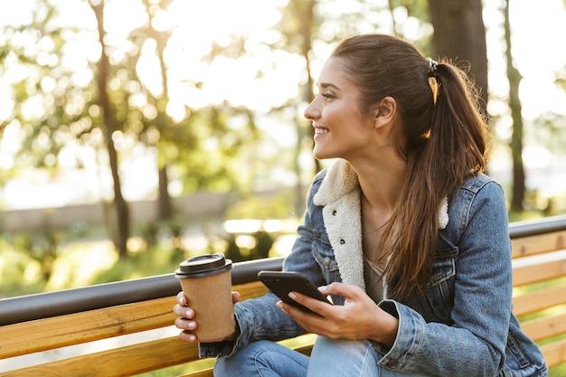 Lächelnde junge frau, die jacke trägt, die auf einer bank im park sitzt, mit handy, kaffee zum mitnehmen trinkend