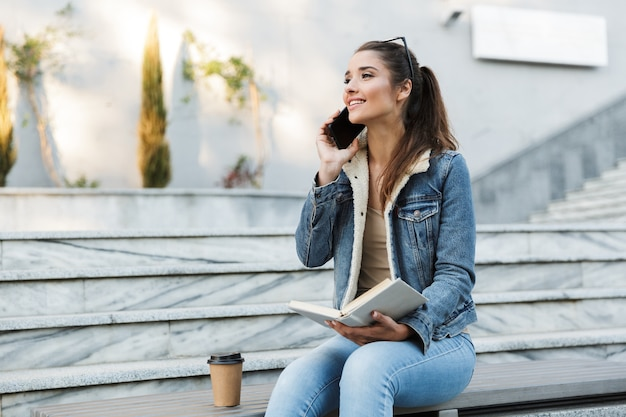 Lächelnde junge frau, die jacke trägt, die draußen auf einer bank sitzt, buch liest, auf handy spricht
