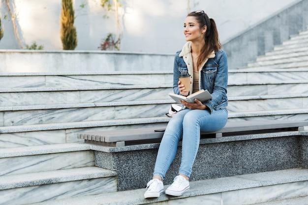 Lächelnde junge frau, die jacke trägt, die draußen auf einer bank sitzt, buch liest und tasse kaffee zum mitnehmen hält