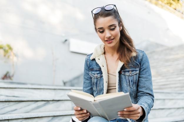 Lächelnde junge frau, die jacke trägt, die draußen auf einer bank sitzt und buch liest