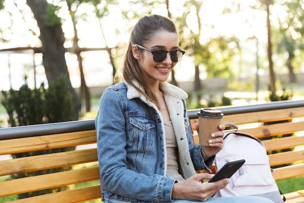Lächelnde junge frau, die jacke und sonnenbrille trägt, die auf einer bank im park sitzen, mit handy, kaffee zum mitnehmen trinkend
