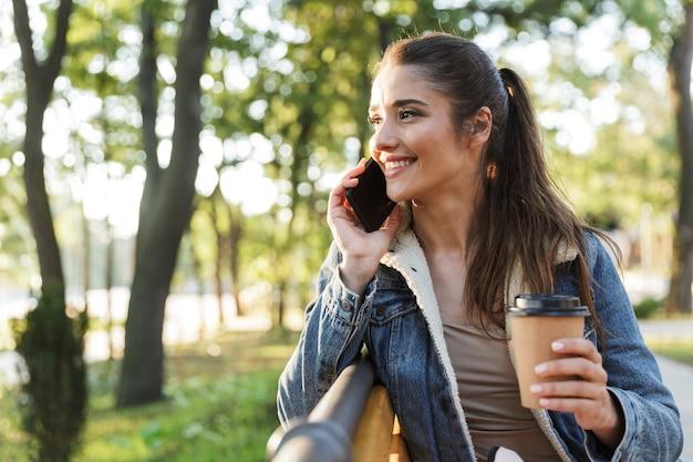 Lächelnde junge frau, die jacke und sonnenbrille trägt, sitzt auf einer bank im park und hält kaffeetasse zum mitnehmen