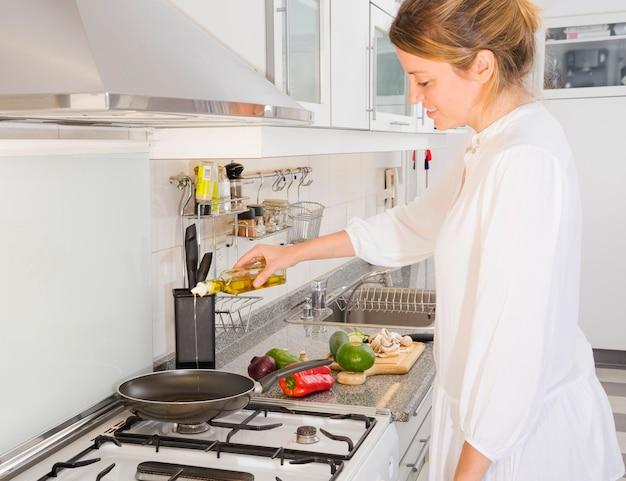Lächelnde junge frau, die lebensmittel in der küche zubereitet
