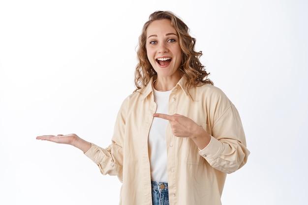 Lächelnde junge frau, die mit ihrem produkt auf ihre hand zeigt, artikel auf ihrer handfläche gegen kopienraum anzeigen und über weißer wand stehend