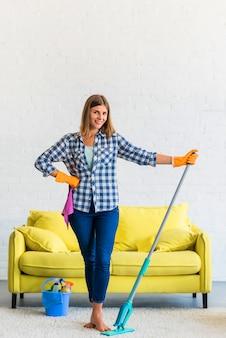 Lächelnde junge frau, die mit mopp und rosa serviette im wohnzimmer steht