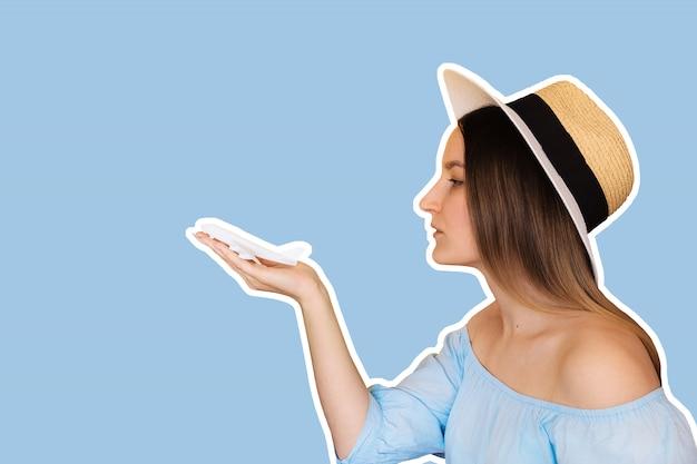 Lächelnde junge frau, die mit spielzeugflugzeug gegen blauen sommerhimmel spielt