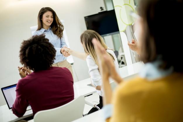 Lächelnde junge frau, die nahes whiteboard steht und ihrem weiblichen kollegen hand rüttelt