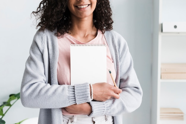 Lächelnde junge frau, die notizbuch an arbeitsplatz hält