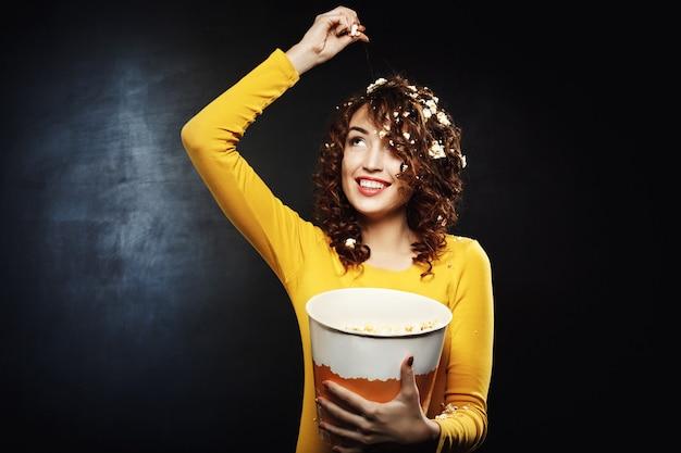 Lächelnde junge frau, die popcorn wirft, das mit breitem lächeln nach oben schaut