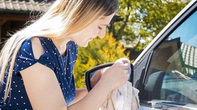 Lächelnde junge frau, die rückspiegel des autos mit stoff säubert.