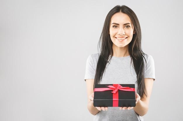 Lächelnde junge frau, die schwarze geschenkbox hält. isoliert über weißem hintergrund.