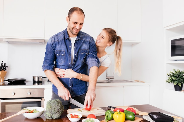 Lächelnde junge frau, die seinen ehemann von hinten umfasst, das gemüse mit messer schneidend