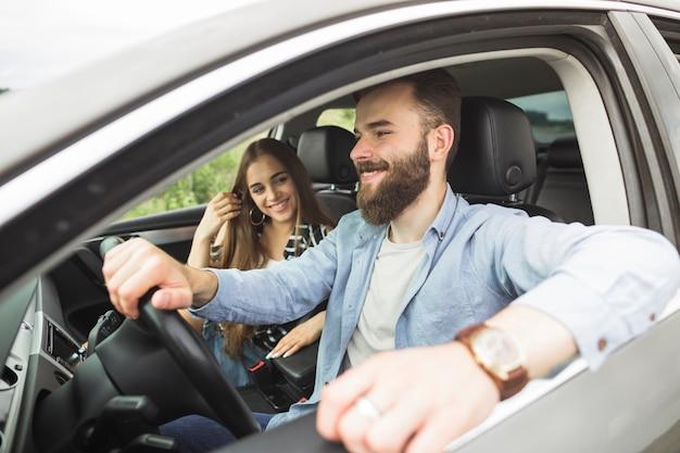 Lächelnde junge frau, die seinen freund fährt auto betrachtet