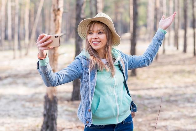 Lächelnde junge frau, die selfie am handy im wald nimmt