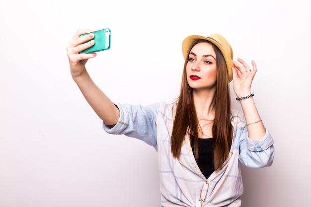 Lächelnde junge frau, die selfie-foto auf smartphone über grau macht