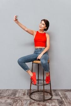 Lächelnde junge frau, die selfie-foto auf smartphone über grauem hintergrund macht