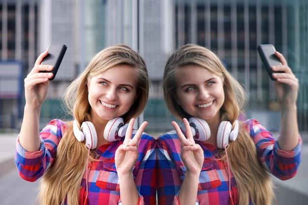 Lächelnde junge frau, die selfie mit friedenshandzeichen nimmt