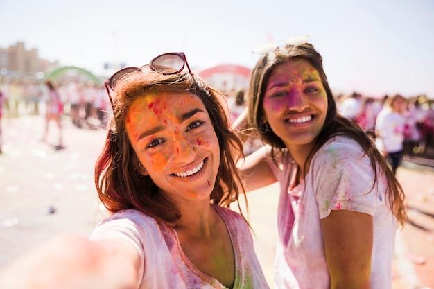 Lächelnde junge frau, die selfie mit ihrem freund in holi nimmt
