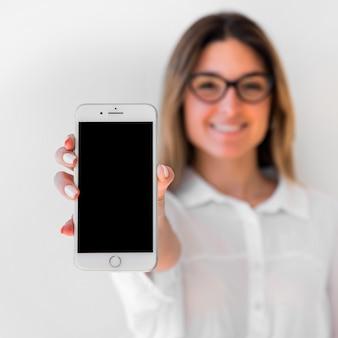 Lächelnde junge frau, die sich smartphonespott zeigt