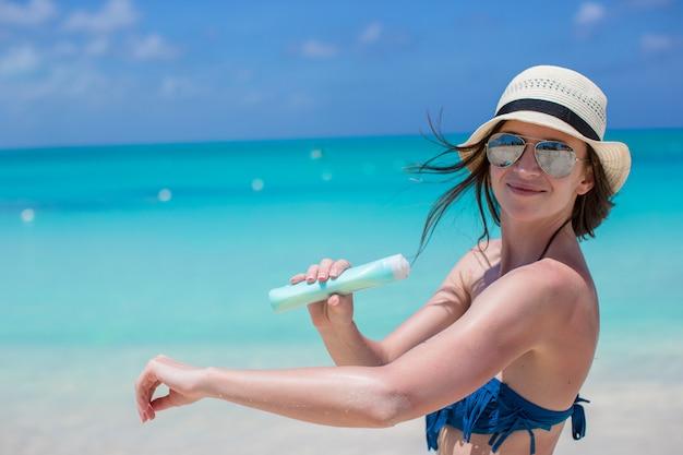 Lächelnde junge frau, die sonnencreme auf strand aufträgt