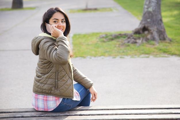 Lächelnde junge frau, die um telefon ersucht und sich zurück in park dreht