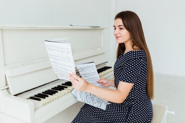 Lächelnde junge frau, die vor dem klavier betrachtet musikalisches blatt sitzt