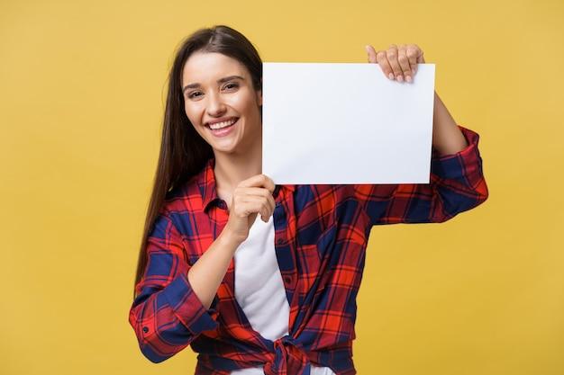 Lächelnde junge frau, die weißbuchblatt hält. studioportrait auf gelbem hintergrund.