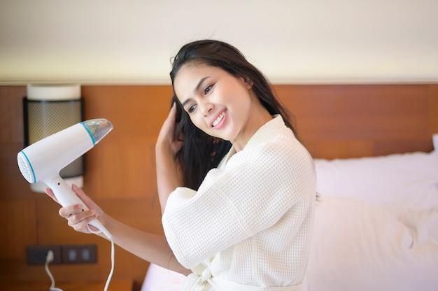 Lächelnde junge frau, die weißen bademantel trägt, der ihr haar mit einem haartrockner nach einer dusche im schlafzimmer trocknet