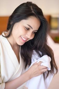 Lächelnde junge frau, die weißen bademantel trägt, der ihr haar mit handtuch nach einer dusche im schlafzimmer abwischt