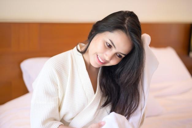 Lächelnde junge frau, die weißen bademantel trägt, wischt ihr haar mit handtuch nach dusche ab