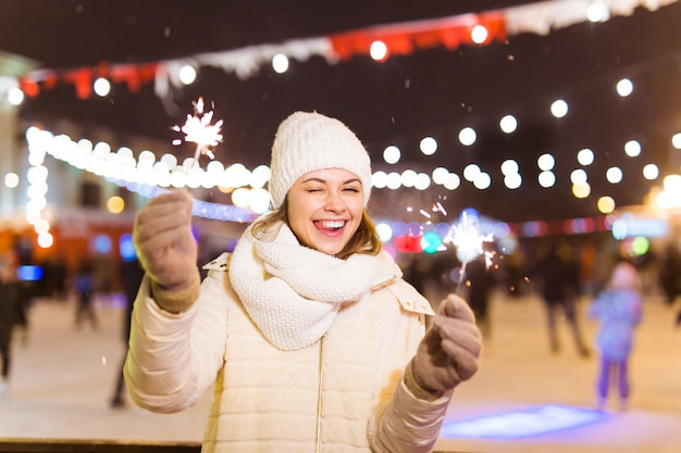 Lächelnde junge frau, die winterstrickkleidung trägt, die wunderkerze im freien über schneehintergrund hält