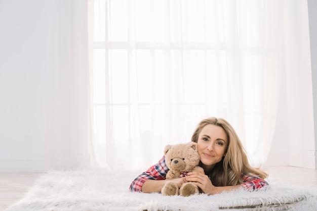 Lächelnde junge frau, die zu hause auf pelz mit teddybären liegt