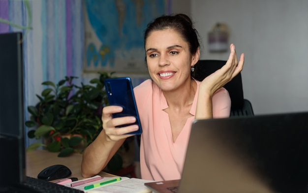 Lächelnde junge frau, die zu hause in der nähe des laptops arbeitet, mit der hand seitwärts zuckt, telefon hält, lächeln, das entschuldigung sagt, kann nicht mit videoanruf helfen. weltkarte im hintergrund