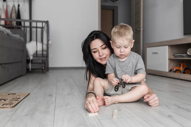 Lächelnde junge frau, die zu hause mit ihrem kleinen sohn spielt