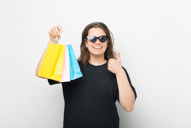 Lächelnde junge frau hält einige einkaufstüten und zeigt daumen nach oben.