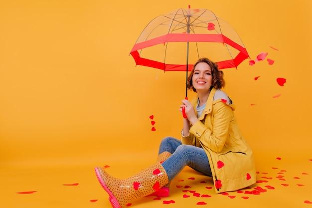 Lächelnde junge frau im gelben mantel, der mit roten herzen an der wand aufwirft. wunderschönes mädchen, das valentinstag feiert und sonnenschirm hält.