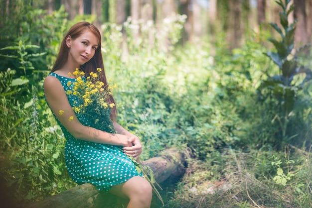 Lächelnde junge frau im grünen kleid, das auf protokoll sitzt und gelbe blumen im wald am sonnigen sommertag hält.