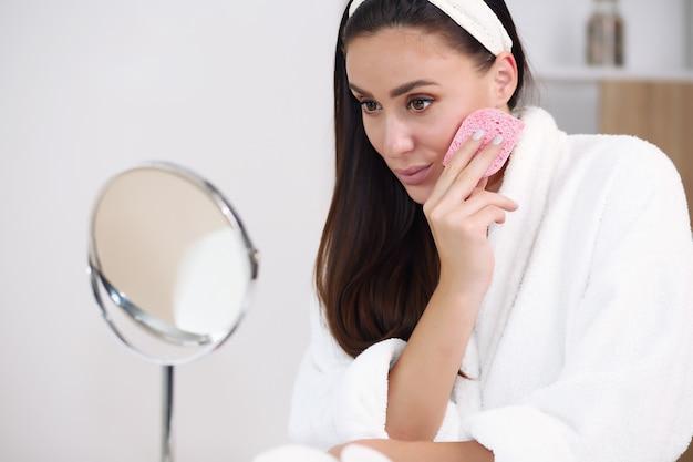 Lächelnde junge frau im haarband, das ihr gesicht berührt und zu hause badezimmer spiegelt