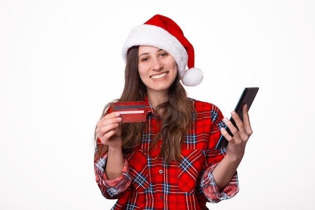 Lächelnde junge frau im karierten roten hemd und in der weihnachtsmütze unter verwendung des handys
