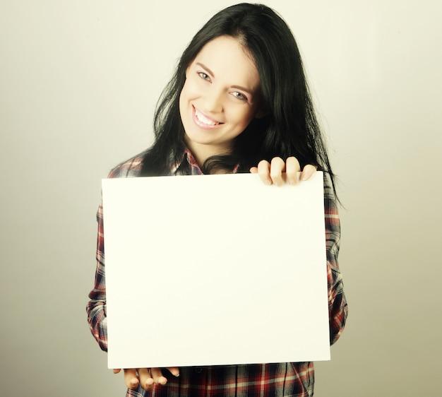 Lächelnde junge frau im lässigen stil, die leeres schild zeigt, über grauem hintergrund isoliert