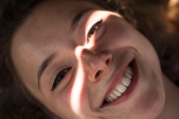 Lächelnde junge frau im schatten mit hellem schimmer