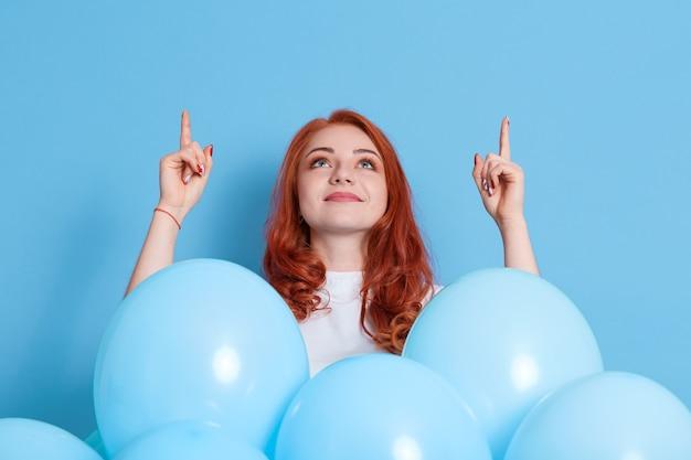 Lächelnde junge frau im weißen rollkragenpullover zeigt zeigefinger mit beiden händen nach oben und feiert und hält blaue luftballons isoliert auf farbwand. geburtstagsfeier.