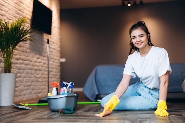 Lächelnde junge frau im weißen t-shirt mit dunkler haarreinigung in gelben gummihandschuhen für handschutz und eimer mit reinigungsmitteln zu hause