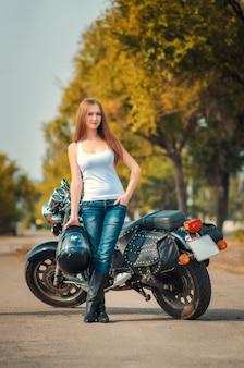 Lächelnde junge frau im weißen t-shirt und in den gläsern auf einem motorrad in der stadt