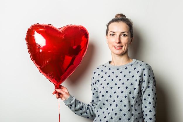 Lächelnde junge frau in einem pullover, der einen herzluftballon auf einem hellen hintergrund hält. valentinstag konzept. banner.