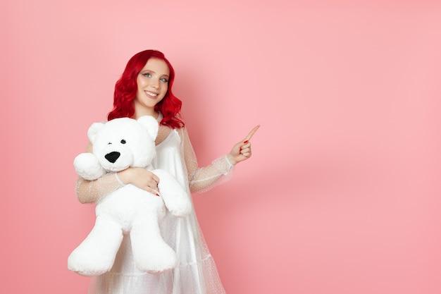Lächelnde junge frau in einem weißen kleid hält einen großen weißen teddybär und zeigt mit dem zeigefinger