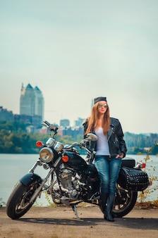 Lächelnde junge frau in einer lederjacke und brille auf einem motorrad in der stadt