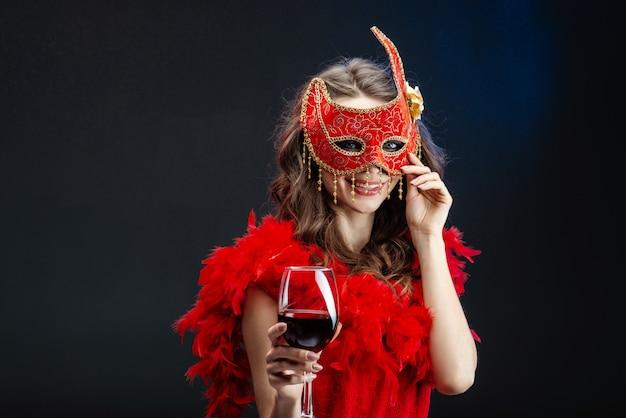 Lächelnde junge frau in einer roten karnevalsmaske und -boa mit einem angehobenen glas wein